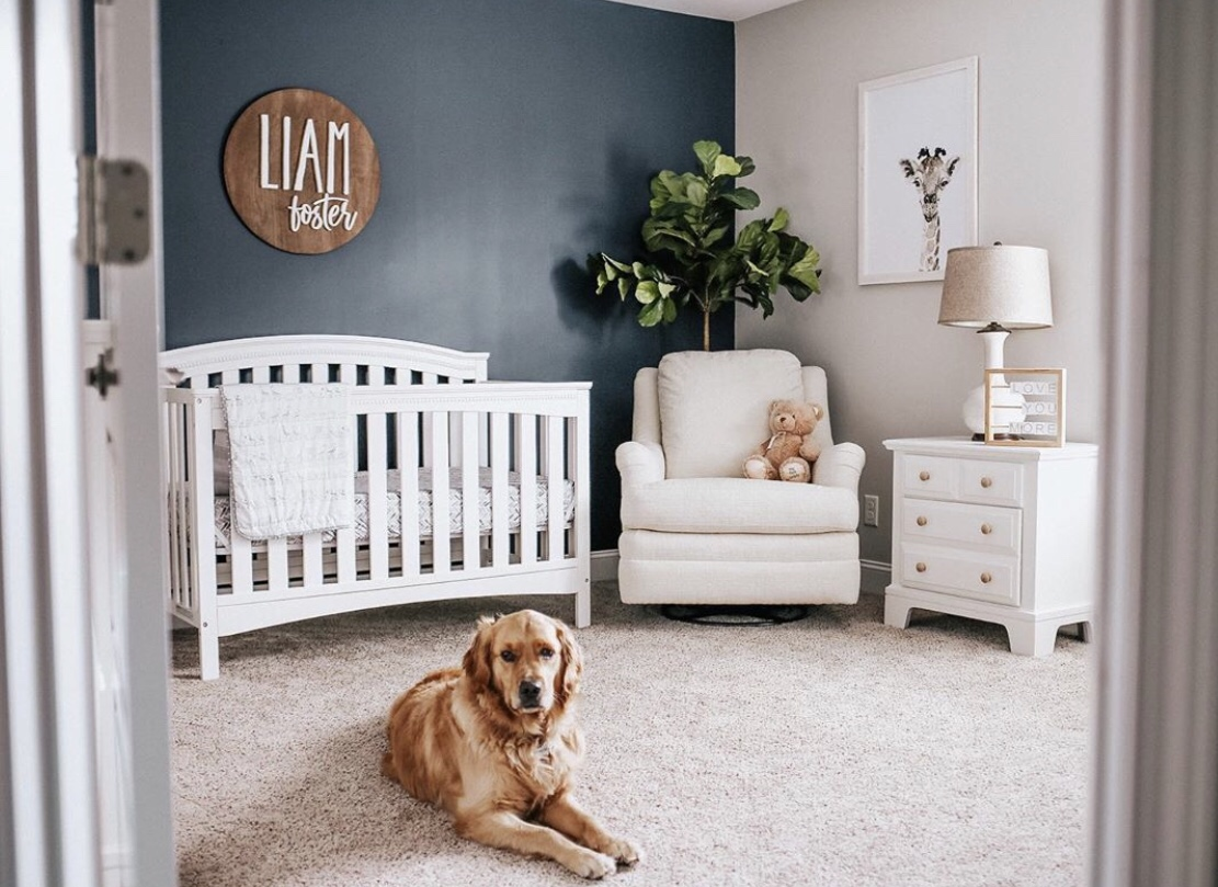 baby room with blue feature wall and white wooden furniture