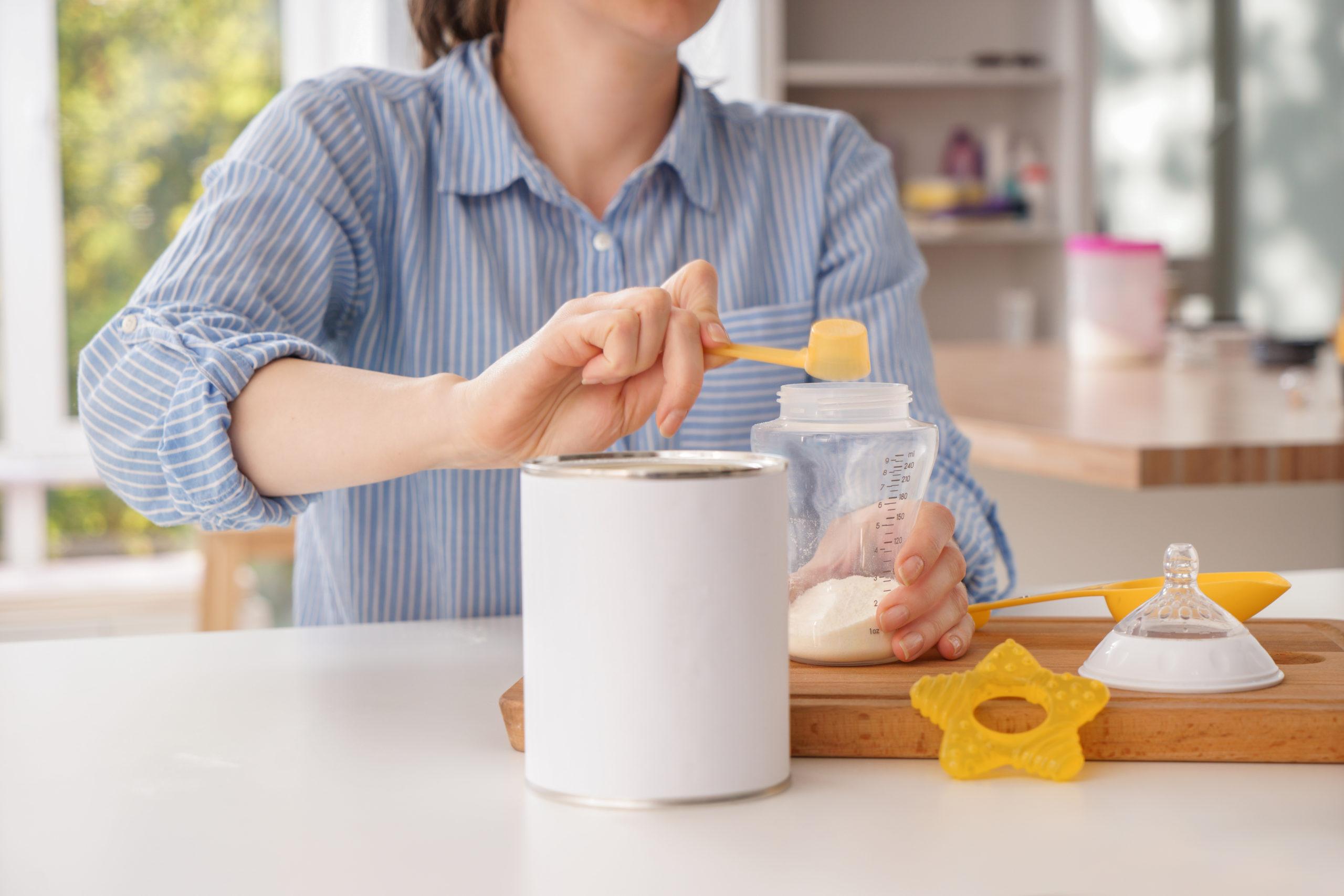 Woman,Preparing,Baby,Formula,At,Table